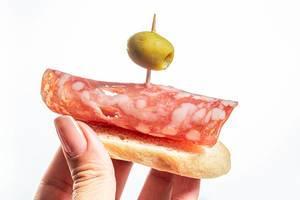 Crostini mit Salami und Olive in der Hand einer Frau vor weißem Hintergrund