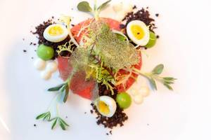 Crudo Nicoise at Chino Latino restaurant: Yellow Fin, Wasabi–Pea Sphere, Black Olive Powder, Quail Egg, Lemon Oil. Top view