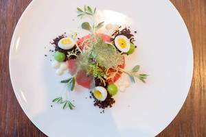 Crudo Nicoise im Chino Latino Restaurant: Gelbflossen Thunfisch, Wasabi–Erbsen Sphäre, Schwarze Oliven Pulver, Wachtel Ei, Zitronen Öl. Draufsicht