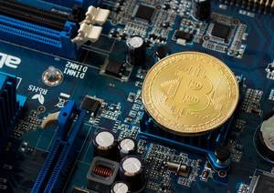Cryptocurrency Bitcoin, golden coin on a blue pc mainboard