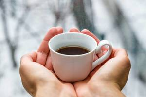 Cup of black coffee in women hands