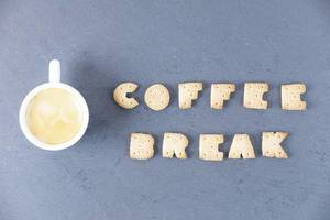 Cup of coffee and Coffee break message written with biscuit letters, dark background