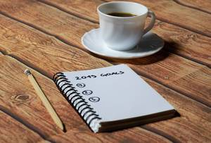 Cup of coffee and notebook on office wood table