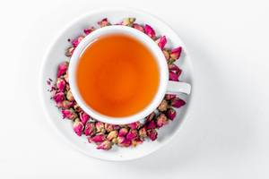 Cup of tea surrounded by dry rose buds