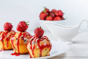 Cupcakes with strawberry sauce and fresh berries on a white plate
