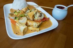 Curry-Pfanne mit Tofu, Pilzen, Karotten Zucchini und frischen Paprika mit Reis aus einem Teller mit Essstäbchen und Chilipaste