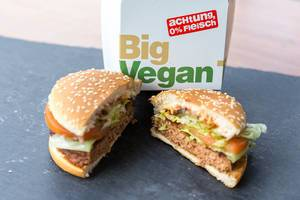 Cut in half Big Vegan TS by McDonalds with a patty based on soy and wheat protein, with salad, vegetables & sesame bread, in front of a burger box