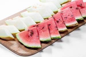 Cut triangular pieces of ripe watermelon and melon on kitchen Board (Flip 2019)