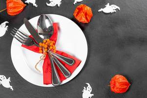 Cutlery on a black background with white ghosts and fruits of physalis. Table setting for Halloween (Flip 2019)