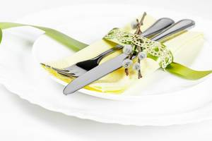 Cutlery on white plates with a napkin and ribbon