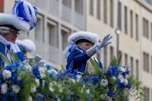 Dame in blau-weißer Uniform wirft Zuschauern Päckchen zu - Kölner Karneval 2018