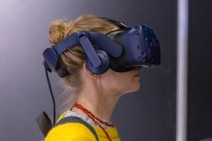 Dame mit gelbem Pullover testet die HTC Vive VR Brille an der Photokina in Köln