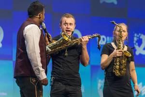 Dan Ram interviewt Trompetenspieler auf der Bühne im Kongresszentrum in München