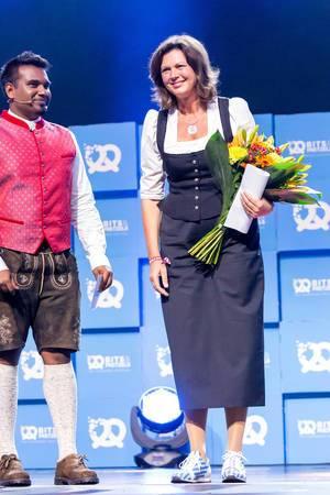 Daniel Ramamoorthy  überreicht Blumen an Ilse Aigner