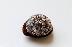 dark chocolate truffle with cocoa powder and chopped hazelnut