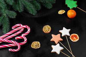 Dark Christmas background with gingerbread and candy lollipops (Flip 2019)