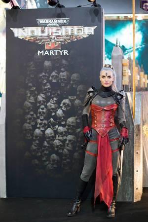 Darstellerin posiert vor dem Plakat Warhammer Inquisitor Martyr
