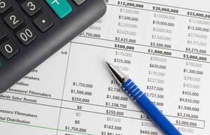 Das finanzielle Wachstum und Buget wird berechnet - Taschenrechner mit Kugelschreiber