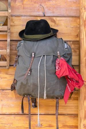 Das Gepäck eines Bergwanderes mit Hut und rotem Tuch an Holzwand