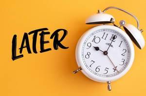 Das Konzept der Prokrastination: Wecker mit dem Text 'Later' vor gelbem Hintergrund