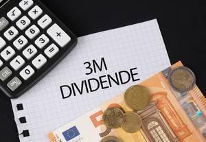 Das Konzept von 3M Dividenden: 3M Dividende Text auf einem Blatt Papier mit einigen Münzen, einem 5-Euro Schein und einem Kalkulator
