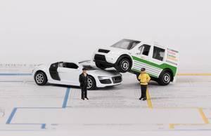 Das Konzept von Autounfall und Versicherung: zwei Spielzeugautos mit Polizisten auf einem Schadensbericht