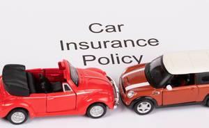 """Das Konzept von Autoversicherung: Text """"Car Insurance Policy"""" auf weißem Hintergrund mit zwei roten Spielzeugautos an einem Unfall beteiligt"""