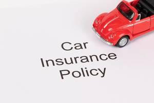 """Das Konzept von Autoversicherung: Text """"Car Insurance Policy"""" mit einem roten Oldtimer-Spielzeugauto"""
