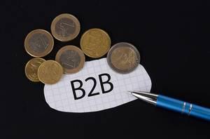 Das Konzept von B2B: B2B Text auf einem Blatt Papier mit einigen Münzen und einem blauen Stift im schwarzen Hintergrund