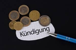 Das Konzept von der Kündigung: Kündigung Text auf einem Blatt Papier mit einigen Münzen und einem blauen Stift im schwarzen Hintergrund