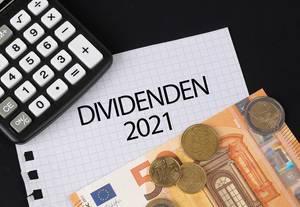 Das Konzept von Dividenden 2021: Dividenden 2021 Text auf einem Blatt Papier mit einigen Münzen, einem 5-Euro Schein und einem Kalkulator