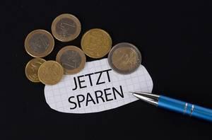 Das Konzept von Geld sparen: Jetzt sparen Text auf einem Blatt Papier mit einigen Münzen und einem blauen Stift im schwarzen Hintergrund