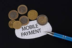 Das Konzept von Mobile Payment: Mobile Payment Text auf einem Blatt Papier mit einigen Münzen und einem blauen Stift im schwarzen Hintergrund