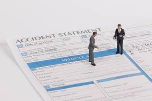 Das Konzept von Schadenmeldung: zwei Menschen besprechen die Schaden nach einem Unfall