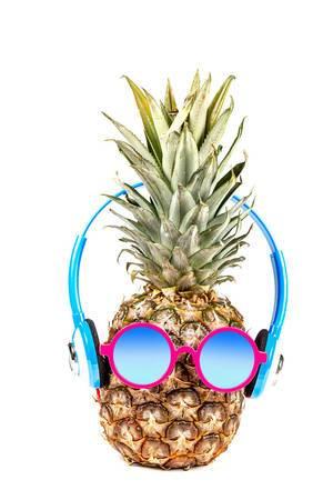 Das Konzept von Sommerurlaub und Erholung: eine Ananas trägt Sonnenbrille und Kopfhörer vor weißem Hintergrund