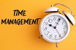 Das Konzept von Zeitmanagement: Wecker mit dem Text 'Time management' vor gelbem Hintergrund