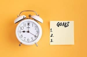 Das Konzept von Zielsetzung: Wecker und ein Zettel mit 'Goals' Text vor gelbem Hintergrund