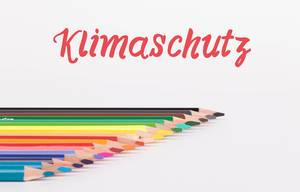 """Das Thema Klimawandel in der Schule: Buntstifte vor weißem Hintergrund mit rotem """"Klimaschutz"""" Text"""