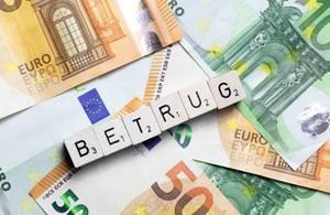 Das Wort Betrug aus Würfelbuchstaben vor Geldscheinen