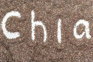 Das Wort Chia in einem Samen-Meer geschrieben, auf einem Holzuntergrund