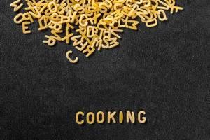 Das Wort Cooking, geschrieben mit Pasta, vor schwarzem Hintergrund
