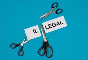 Das Wort Illegal auf einem durchgeschnittenem Papier mit Scheren auf blauem Hintergrund