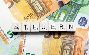 Das Wort Steuern aus Würfelbuchstaben auf Geldscheinen