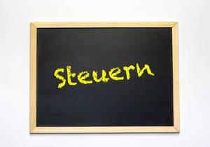 Das Wort Steuern in gelb auf einer Tafel