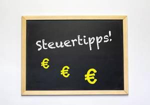 Das Wort Steuertipps! mit Eurozeichen auf einer Tafel