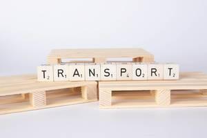 Das Wort TRANSPORT gebildet aus Würfeln auf Holzpaletten vor weißem Hintergrund