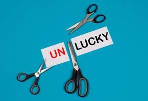 Das Wort Unlucky auf einem durchgeschnittenem Papier mit Scheren auf blauem Hintergrund