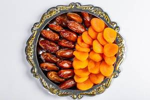 Dates and dried apricots on a tray on a white background. Top view (Flip 2019)