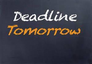DEADLINE TOMORROW mit weißer und oranger Schrift auf schwarze Tafel geschrieben
