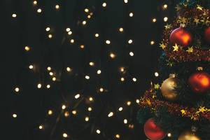 Decorated Christmas tree and luminous garland behind